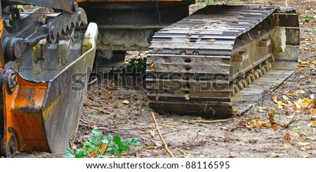 A construction Excavator bucket and track used for excavating of trees debris and anything else needed resting on the ground outside in the woods with room for your text. - stock photo