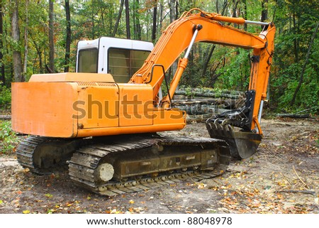 A construction Excavator used for excavating of trees debris and anything else needed resting on the ground outside in the woods with room for your text. - stock photo
