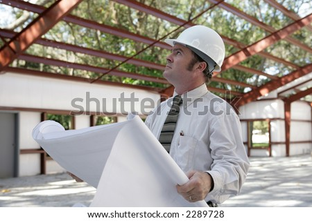A construction inspector holding blueprints and looking at the roof beams of a steel building in progress. - stock photo