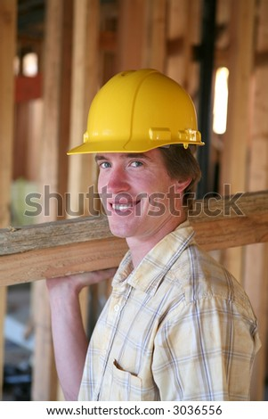 A construction man working building a home and carrying some wood - stock photo