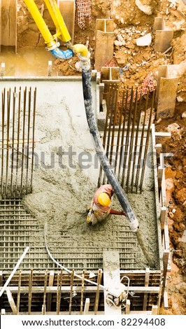 A construction worker directing a hose, pumping concrete at a high flow rate, into a corner of a foundation block, which is almost completely filled up.