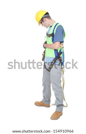 A construction worker double checks fastenings on a safety climbing harness dressed in other safety gear and isolated on white. - stock photo