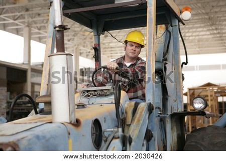 A construction worker driving an earth mover on a construction site. - stock photo