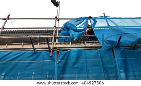 A construction worker is standing on a scaffold deck to fix on the pieces of blue scaffold netting with cable ties to the scaffold. This will prevent debris from flying out from the scaffold mesh.