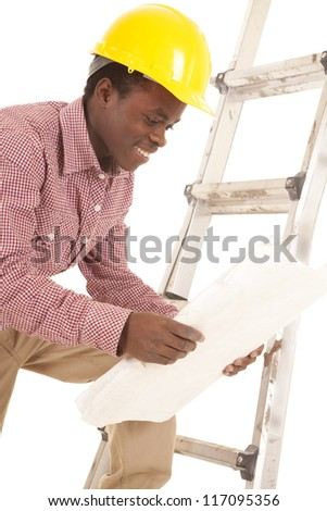 A construction worker looking at his plans with a smile on his face - stock photo