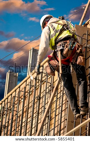 A construction worker on a high wall against colorful sunrise clouds.