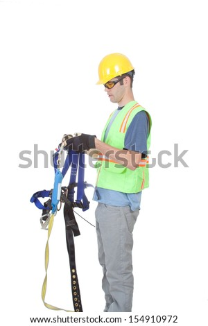 A construction worker puts on a safety climbing harness dressed in other safety gear and isolated on white. - stock photo
