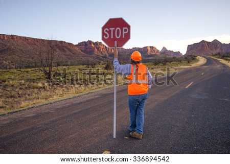 A construction worker stopping traffic, holding a stop sign. - stock photo