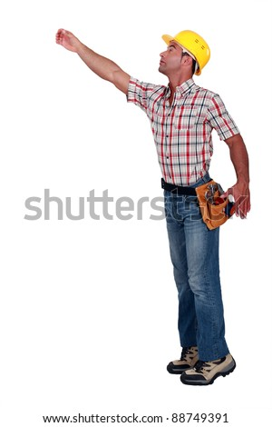 A construction worker trying to reach for something. - stock photo