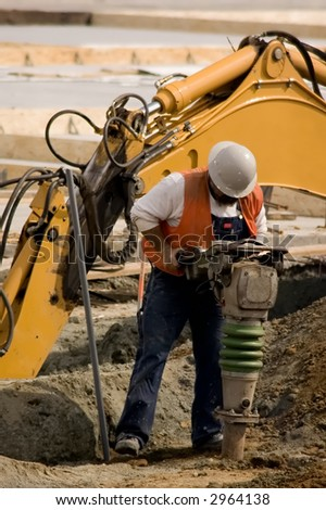 A construction worker using a large soil tamping machine - stock photo