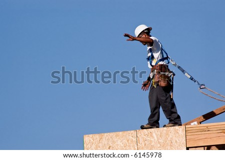 A construction worker walking across the top edge of a second story wall. - stock photo
