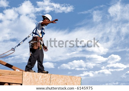 A construction worker walking across the top edge of a second story wall against a cloudy sky. - stock photo