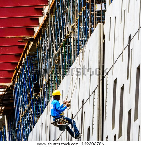 A Construction Workers high up on the wall of a new building. - stock photo