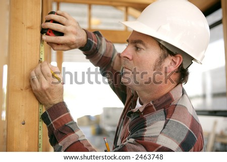 A construction working taking measurments and marking a wood beam on a house frame.