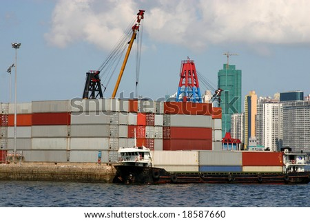 A container barge being loaded with containers in Victoria Harbour - Hong Kong