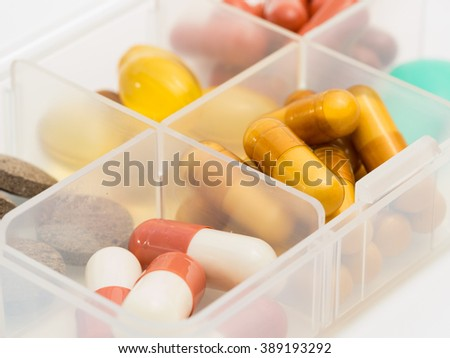 A container for pills with different medicines. - stock photo