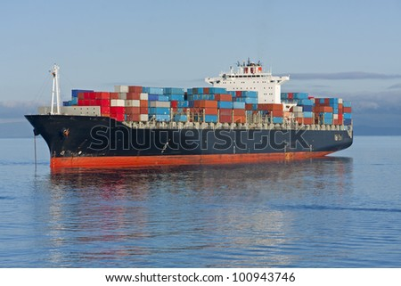 A container ship anchored in a harbour. - stock photo