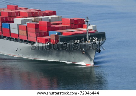A container ship arriving in port on a very calm day. - stock photo