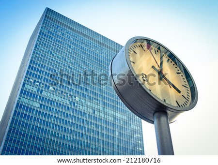 A contemporary skyscraper in the London Docklands business district with a clock in the foreground marking the time.