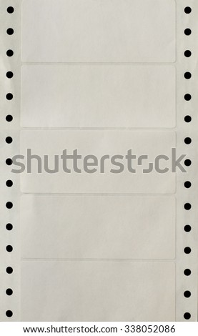 A continuous vertical strip of blank white computer printer address labels with punched holes for sprocket feed mechanism on either side . - stock photo
