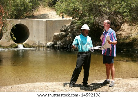 a contractor and client view plans at a construction site - stock photo
