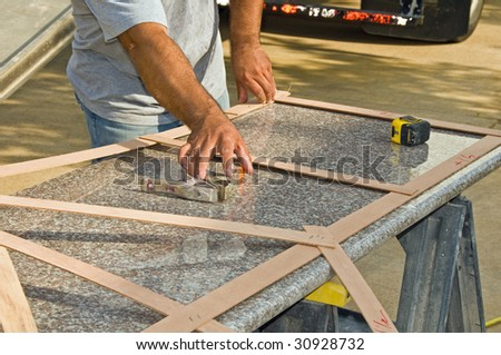 A contractor measures granite for use in a kitchen remodeling - stock photo