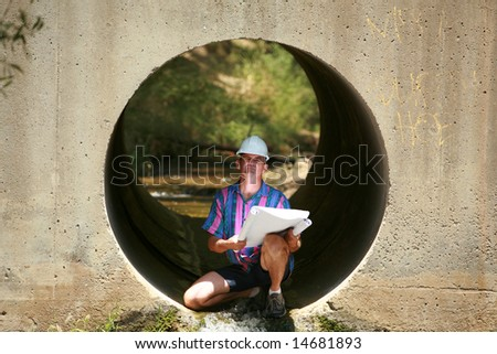 a contractor views blue prints while on a construction site - stock photo