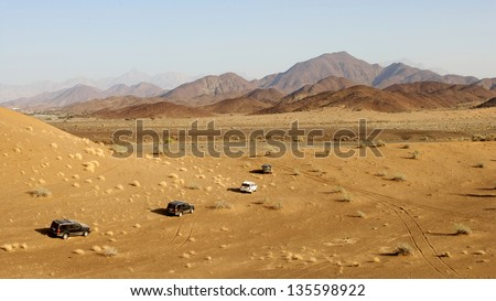 A convoy of 4x4 vehicles driving offroad in Oman.