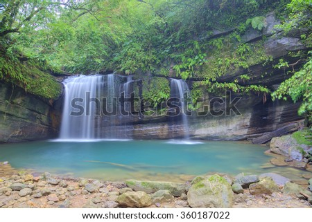 A cool refreshing waterfall pouring into an emerald pond hidden in a mysterious forest of lush greenery ~ Beautiful river scenery of Taiwan - stock photo