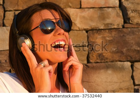 A cool young woman listens to music on some headphones