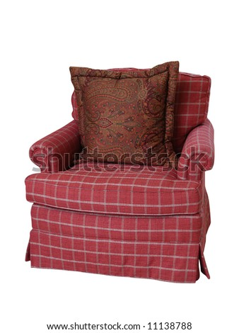 A coral colored plaid overstuffed armchair with a paisley pillow isolated on white. - stock photo
