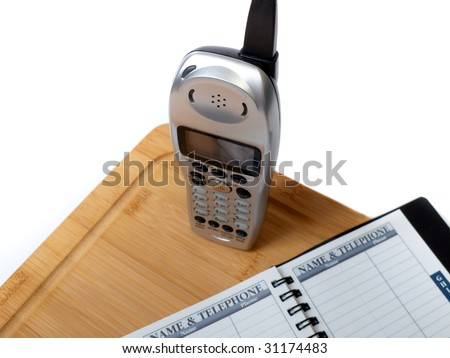 A cordless phone on a cutting board, with a blank name and telephone directory, isolated on white. - stock photo