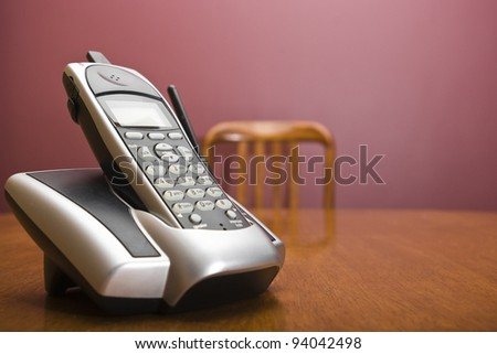 A cordless phone on a table with an out of focus chair - stock photo