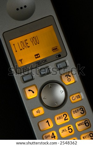A cordless phone with a love message on the illuminated LCD screen