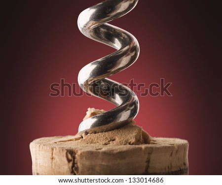 A corkscrew spiked in a wine stopper open. - stock photo