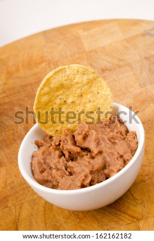 A Corn Chip Dipped into Refried Beans in Ceramic Ramekin - stock photo