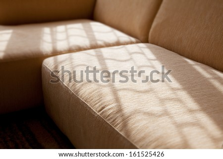 A corner sofa in a beige color with some sunlight on it. - stock photo
