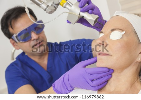 A cosmetic surgeon doctor giving fractional CO2 laser skin treatment to the face of a senior female woman patient - stock photo
