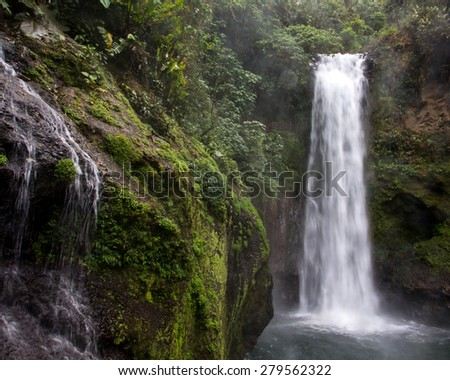 A  Costa RIca Jungle waterfall sprays mist on the surrounding greenery.   - stock photo