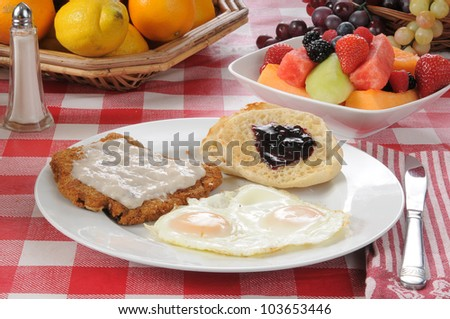 A country fried steak and egg breakfast with fruit salad
