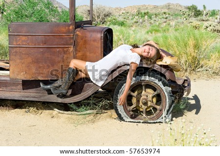 A country girl resting on the fender of an old car in a remote desert.