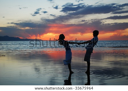 A couple dancing at a lake during a sunset. - stock photo