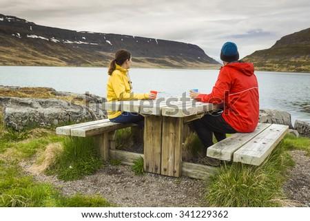 A couple drinking tea close to a beautiful lake - stock photo