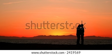 A couple embraces while watching the sunset on a California beach. - stock photo