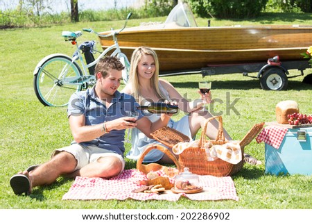 A couple enjoys a summer picnic by the lake in a country setting - stock photo