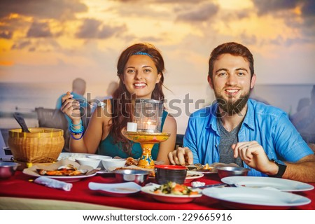A couple having dinner on the Jimbaran beach in Bali (looking at camera) - stock photo