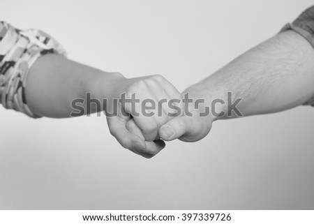 A couple holding hands in front of a grey background