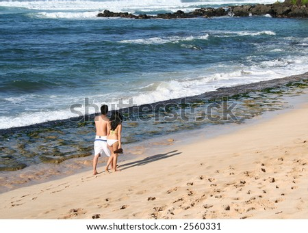 A couple holding hands walking on the beach