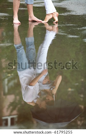A couple hugging under umbrella reflected in a puddle - stock photo