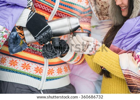 A couple in love in a snowy park. Valentine's Day. Asian Girl, a European man. - stock photo